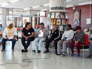 Descrição de imagem: Foto de seis participantes do evento. Eles estão sentados em roda. Ao centro, Seu Zeca fala ao microfone e, à esquerda, outro participante lê um livro Braille. No fundo da sala, há alguns livros dispostos em prateleiras.