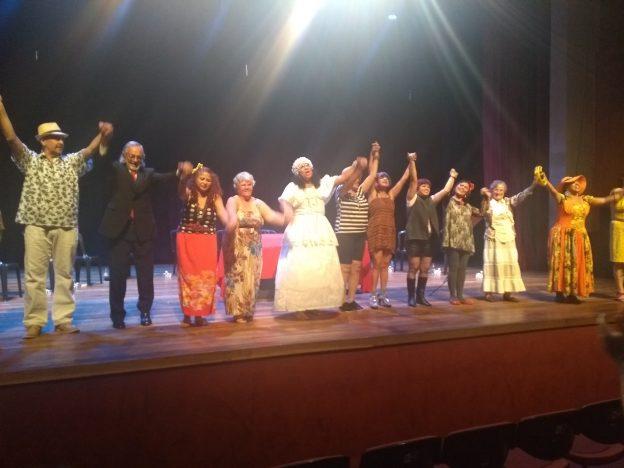Descrição de imagem: Foto de 11 atores em cima de um palco. Eles estão de mãos dadas e erguidas. Da esquerda para a direita há um homem de chapéu de palha e camisa estampada; um homem de terno; uma mulher de cabelos longos e vermelhos e com saia da mesma cor; uma senhora de vestido longo e florido; uma mulher com vestido branco; uma pessoa de camisa listrada; uma mulher de vestido; uma pessoa de roupa e botas pretas; uma mulher de flor vermelha na cabeça; uma senhora de vestido branco e uma mulher de chapéu grande e vestido colorido.