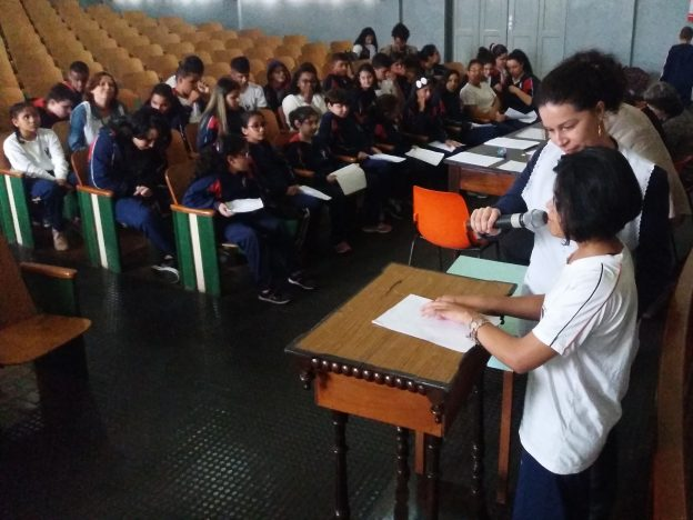 Descrição de imagem: Foto de um auditório com dezenas de crianças sentadas na plateia. À direita da foto, em primeiro plano, está uma menina em pé em frente a uma mesa. Ela lê uma folha em Braille e uma professora está ao seu lado segurando um microfone.