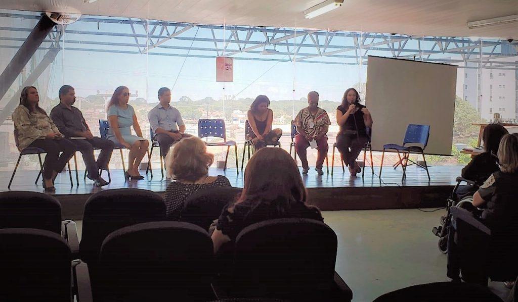 Descrição de imagem: Foto de sete palestrantes em cima de um palco, cinco mulheres e dois homens, e parte da plateia. Ao fundo há uma parede de vidro que mostra parte da cidade.